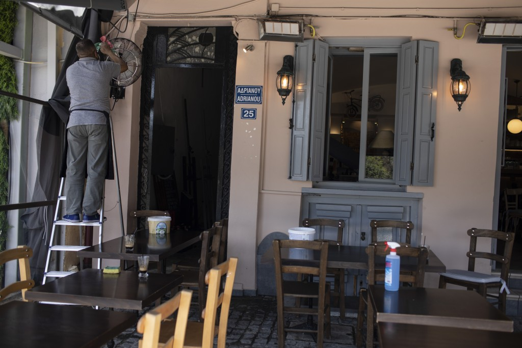 A man cleans a fan outside a coffee shop in Athens' Monastiraki district, Friday, April 30, 2021. COVID-19 restrictions will be relaxed in Greece afte...