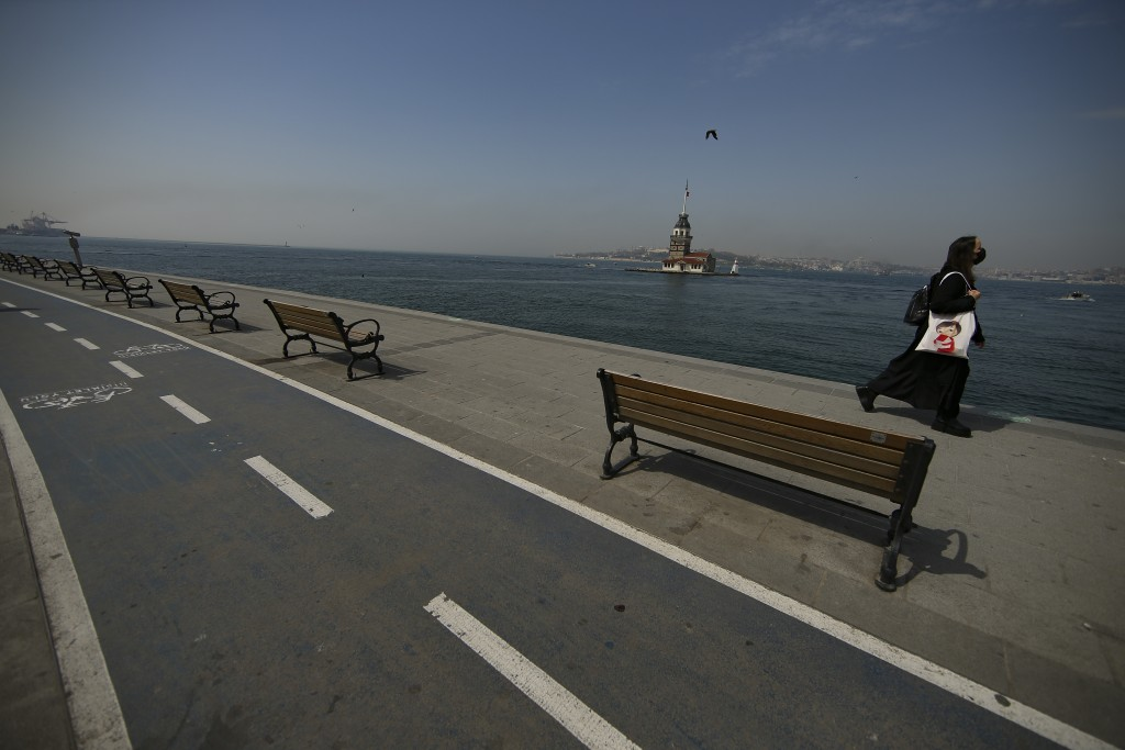 Backdropped by the Maiden's Tower a woman walks on a nearly deserted promenade by the Bosphorus Strait in Istanbul, Friday, April 30, 2021, on the fir...