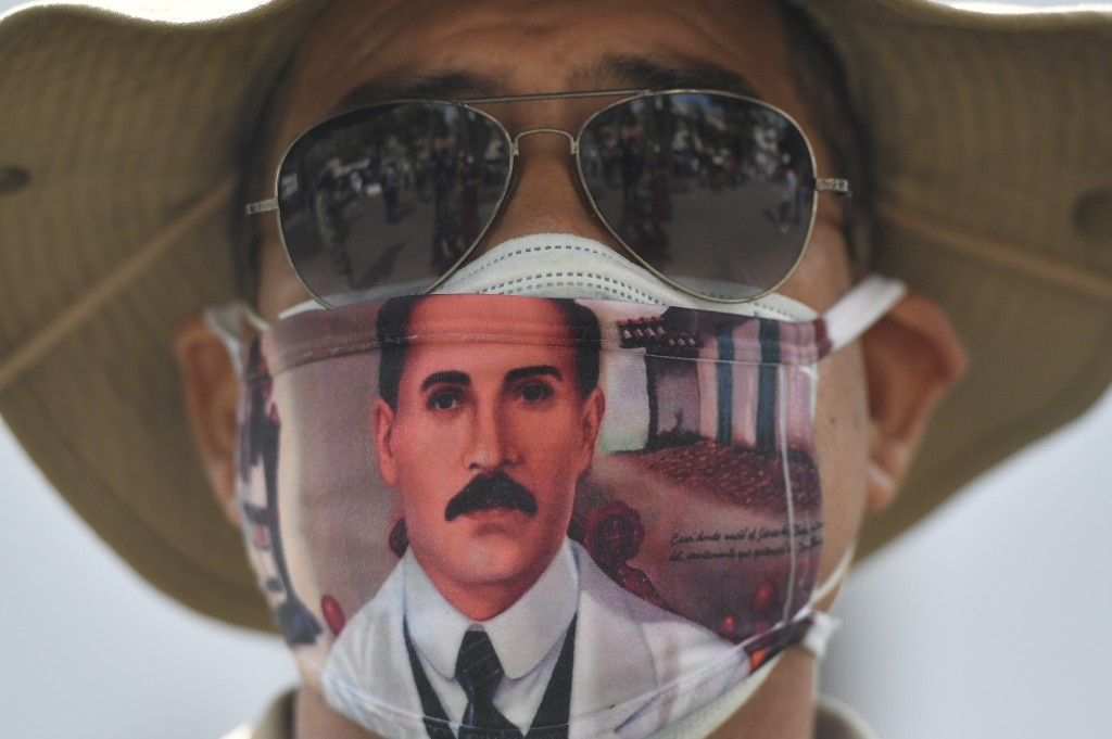 A man wears a mask featuring the image of the late, Venezuelan Dr. Jose Gregorio Hernandez, on the day of his Beatification ceremony outside the churc...