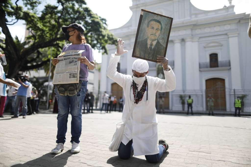Yeni Vasquez raises a portrait of the late, Venezuelan Dr. Jose Gregorio Hernandez outside the church in La Candelaria after the church bell rang, sig...