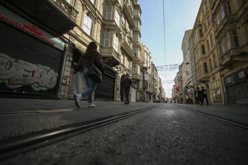 People walk on a virtually empty Istiklal Street, the main shopping street of Istanbul, with shops closed, Friday, April 30, 2021, on the first day of...