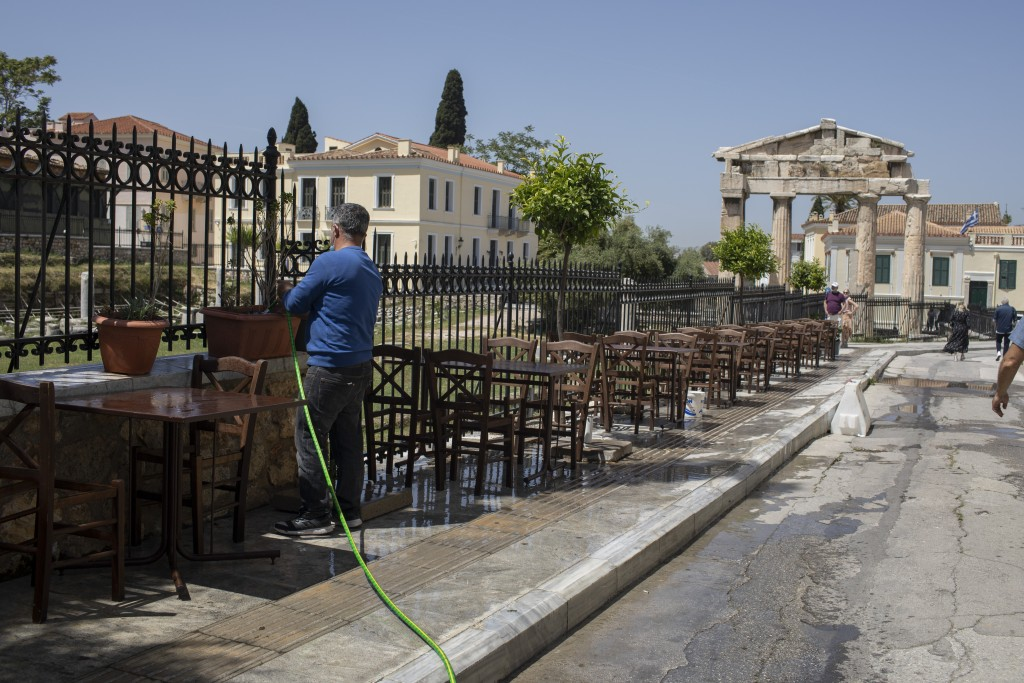 A man cleans with a water hose outside a traditional restaurant in front of the Roman Agora Gate, in Plaka, district of Athens, Friday, April 30, 2021...