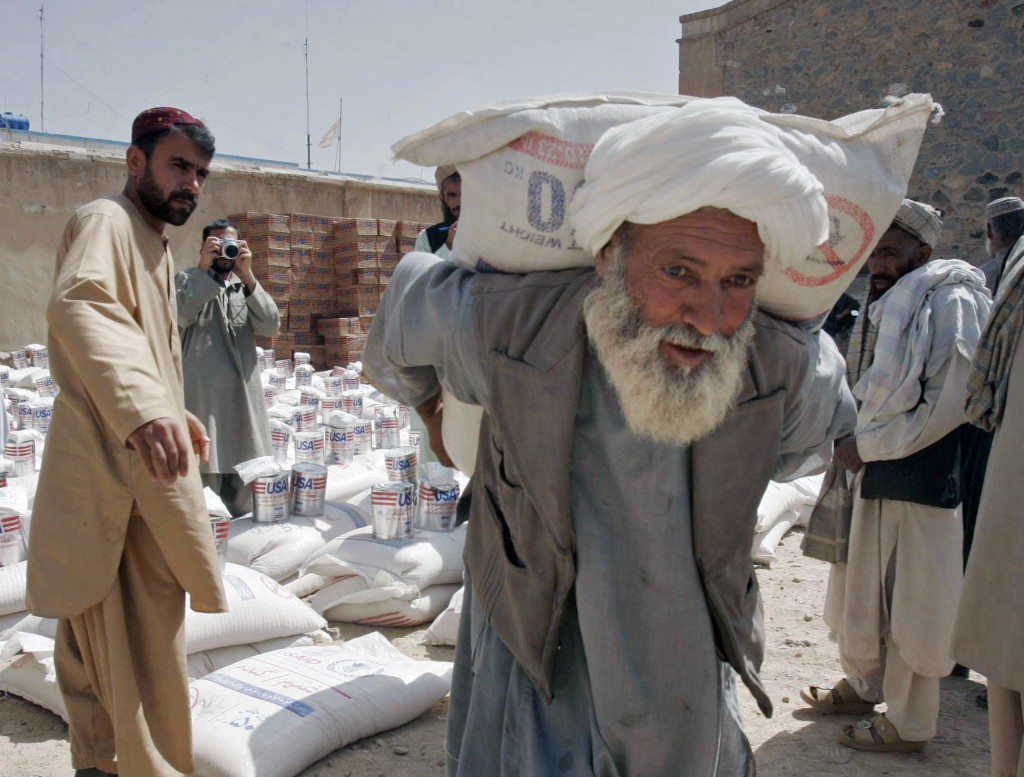 FILE - In this May 10, 2009 file photo, a man carries a sack of wheat distributed to poor displaced families, distributed by World Food Program with t...