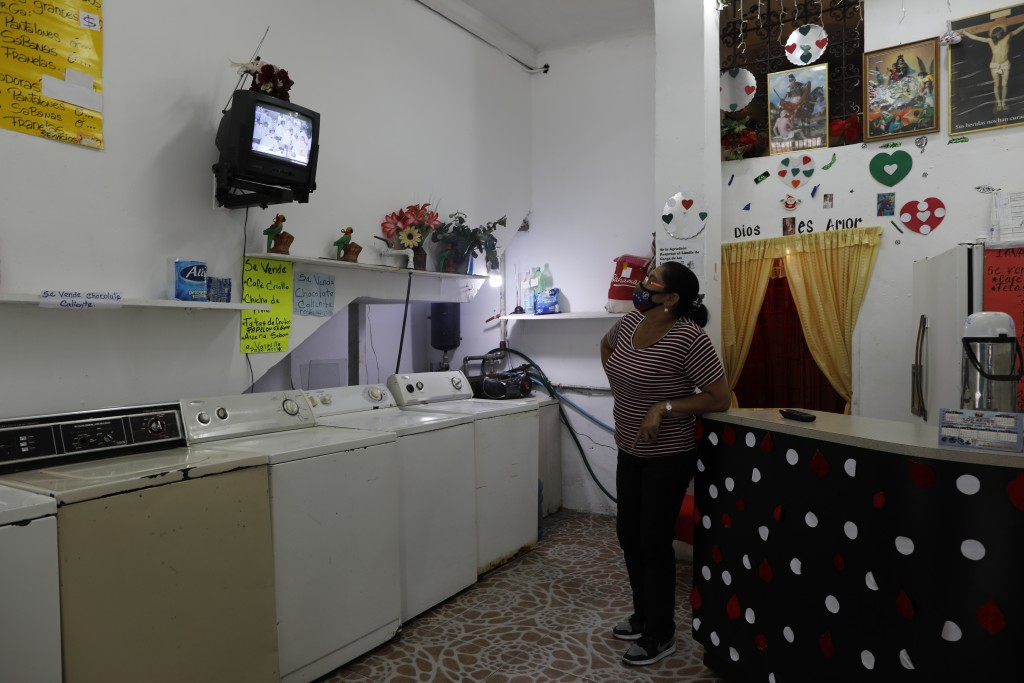 Maria Comedor watches a live television broadcast of the Beatification ceremony for the late, Venezuelan Dr. Jose Gregorio Hernandez inside her washat...