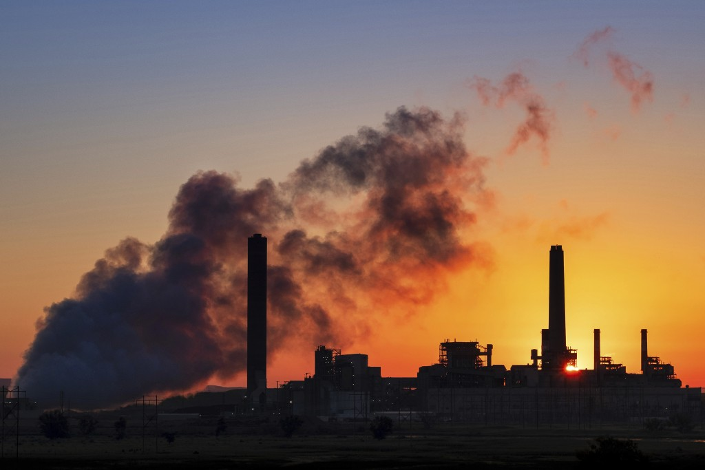 FILE - In this July 27, 2018, file photo, the Dave Johnson coal-fired power plant is silhouetted against the morning sun in Glenrock, Wyo. A law signe...