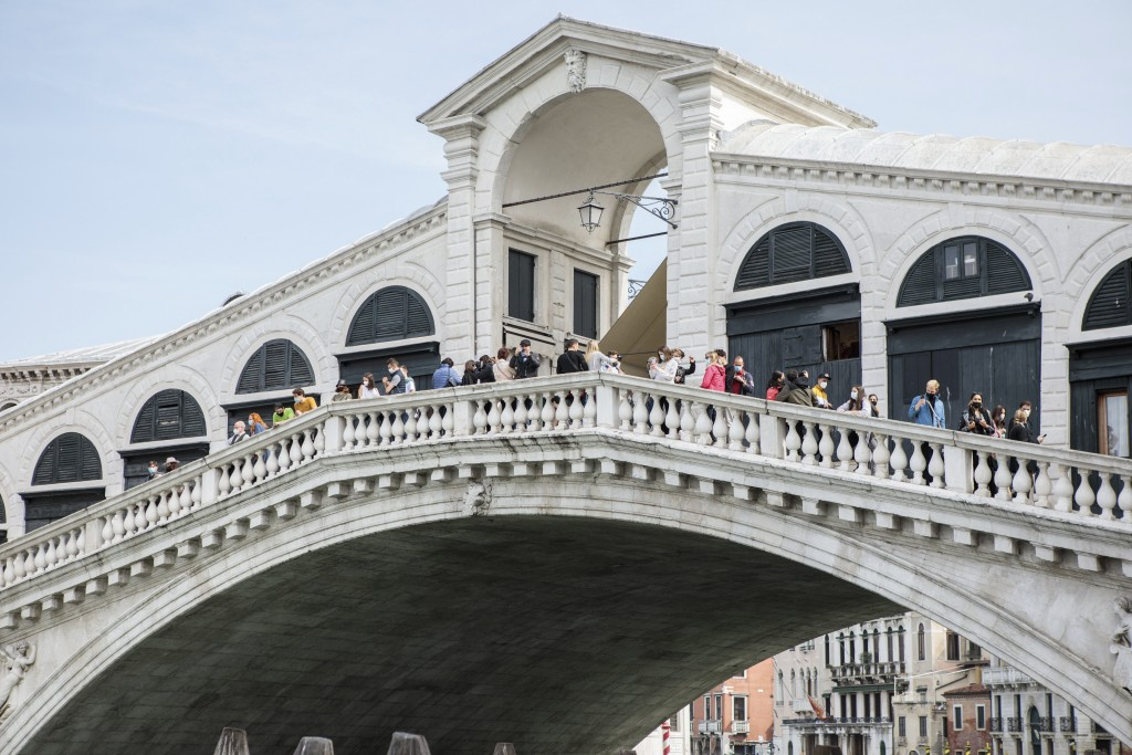 People visit the Rialto bridge in Venice, northern Italy, Saturday, May 1, 2021. Italy is gradually reopening after six months of rotating virus closu...