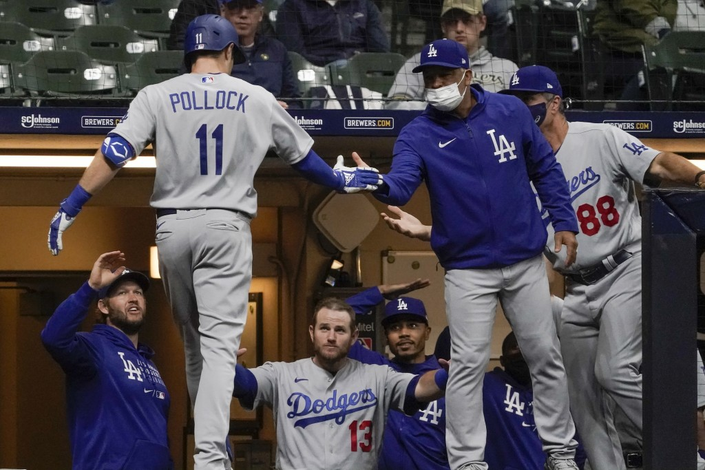 Los Angeles Dodgers' AJ Pollock is congratulated by manager Dave Roberts after hitting a home run during the fifth inning of a baseball game against t...