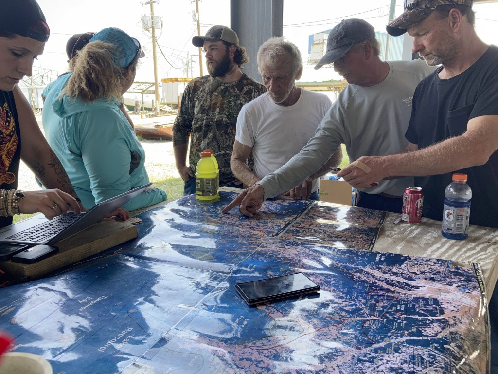 Volunteers gather around a map of the Louisiana coast on Thursday, April 30, 2021, in Cocodrie, La., as they search for survivors of the Seacor Power,...