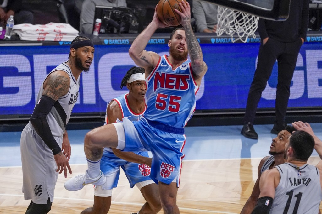 Brooklyn Nets guard Mike James (55) goes to the basket past Portland Trail Blazers forward Carmelo Anthony, left, and center Enes Kanter (11) during t...