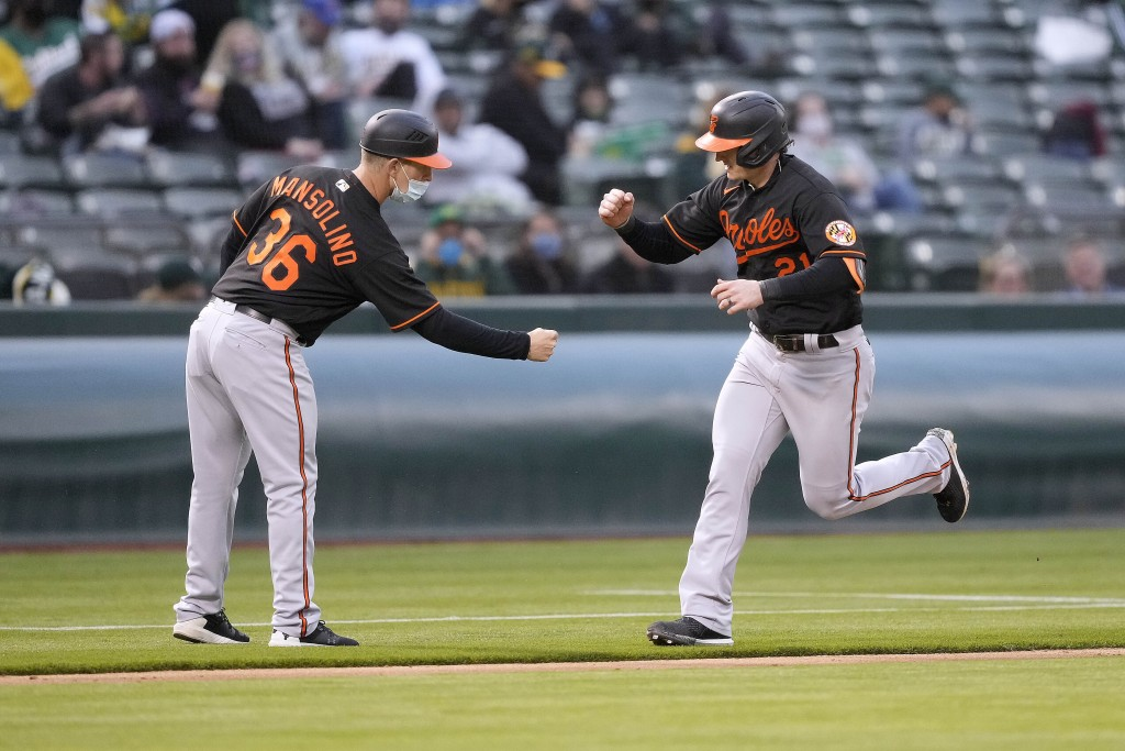 Baltimore Orioles' Austin Hays (21) is congratulated by third base coach Tony Mansolino (36) as he rounds the bases after hitting a solo home run agai...
