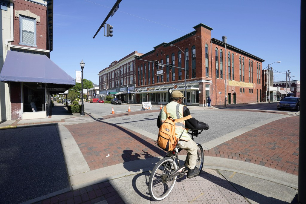 FILE - In this April 22, 2021 file photo, a man rides a bicycle downtown in Elizabeth City, N.C.  The fatal shooting of a Black man by sheriff's deput...