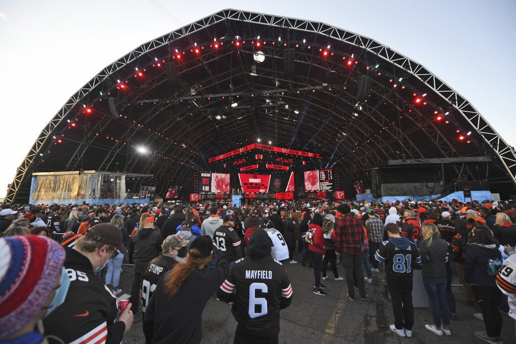 Fans watch the from the outside of the NFL Draft Theatre during the second round of the NFL football draft, Friday, April 30, 2021, in Cleveland. (AP ...