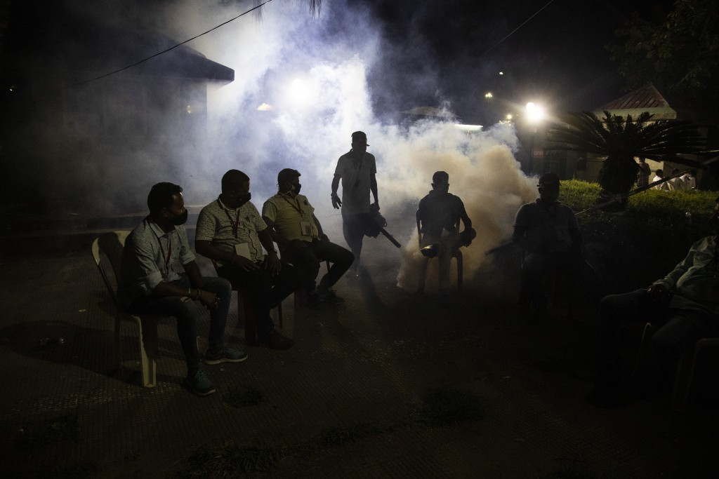 A municipal worker fumigates as supporters of Bharatiya Janata Party wait outside a vote counting center in Gauhati, India, Sunday, May 2, 2021. Preli...