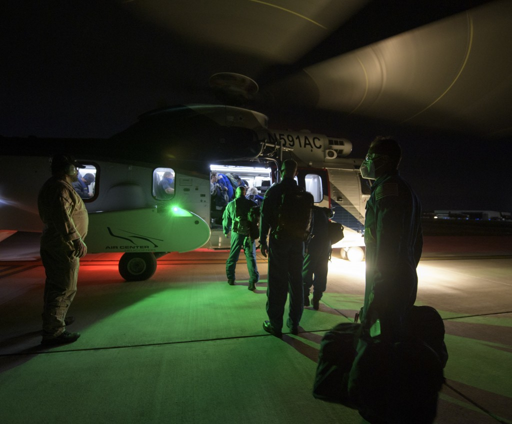 In a photo provided by NASA, NASA and SpaceX support teams board a helicopter at Pensacola, Fla., Saturday, May 1, 2021, to head to a ship in the Gulf...