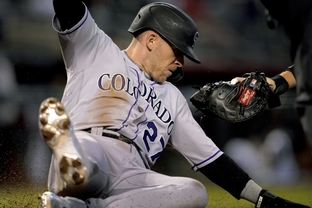 Colorado Rockies' Trevor Story (27) slides safely around the glove of Arizona Diamondbacks catcher Carson Kelly on a base hit by Ryan McMahon during t...