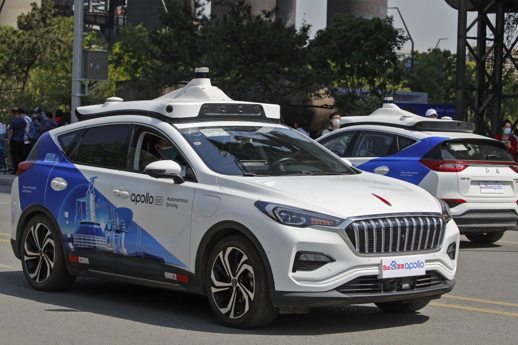 Baidu Apollo Robotaxis move on a street at the Shougang Park in Beijing, Sunday, May 2, 2021. Chinese tech giant Baidu rolled out its paid driverless ...