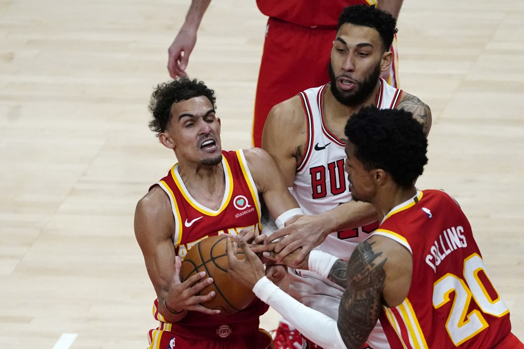Atlanta Hawks guard Trae Young, left, and John Collins (20) battle Chicago Bulls guard Denzel Valentine (45) in the second half of an NBA basketball g...