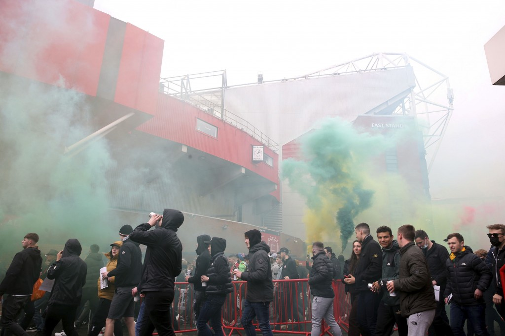 Fans make their way past barriers outside the ground as they let off flares whilst protesting against the Glazer family, owners of Manchester United, ...