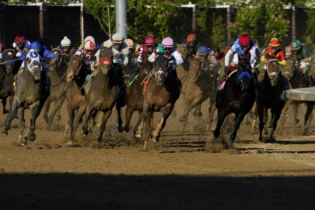 John Velazquez riding Medina Spirit, third from right, leads the field as they round the fourth turn to win the 147th running of the Kentucky Derby at...