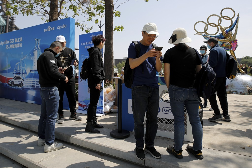 People using their smartphones to book a ride for the Baidu Apollo Robotaxi at a passenger pickup point setup at the Shougang Park in Beijing, Sunday,...