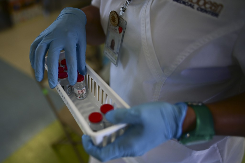 FILE - In this March 10, 2021 file photo, a nurse carries vials of the Moderna COVID-19 vaccine during a mass vaccination campaign, at the Maria Simmo...