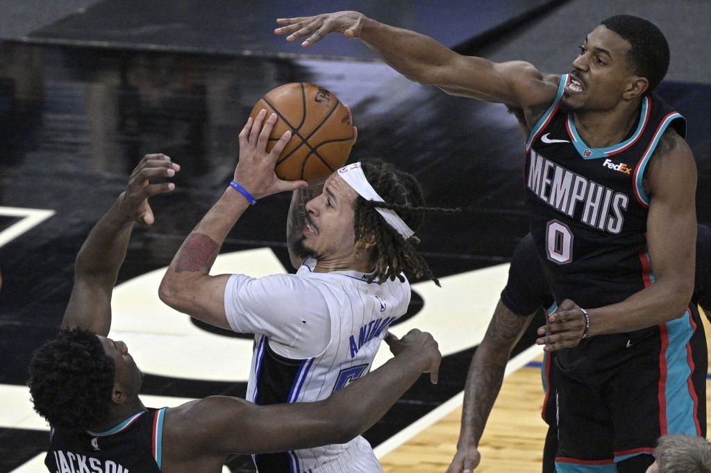 Orlando Magic guard Cole Anthony is fouled by Memphis Grizzlies forward Jaren Jackson Jr., left, while going up to shoot as Grizzlies guard De'Anthony...