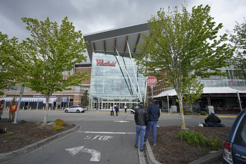 Shoppers evacuated from the Westfield Southcenter Mall stand in a parking lot following a reported shooting, Saturday, May 1, 2021, at the mall in Tuk...