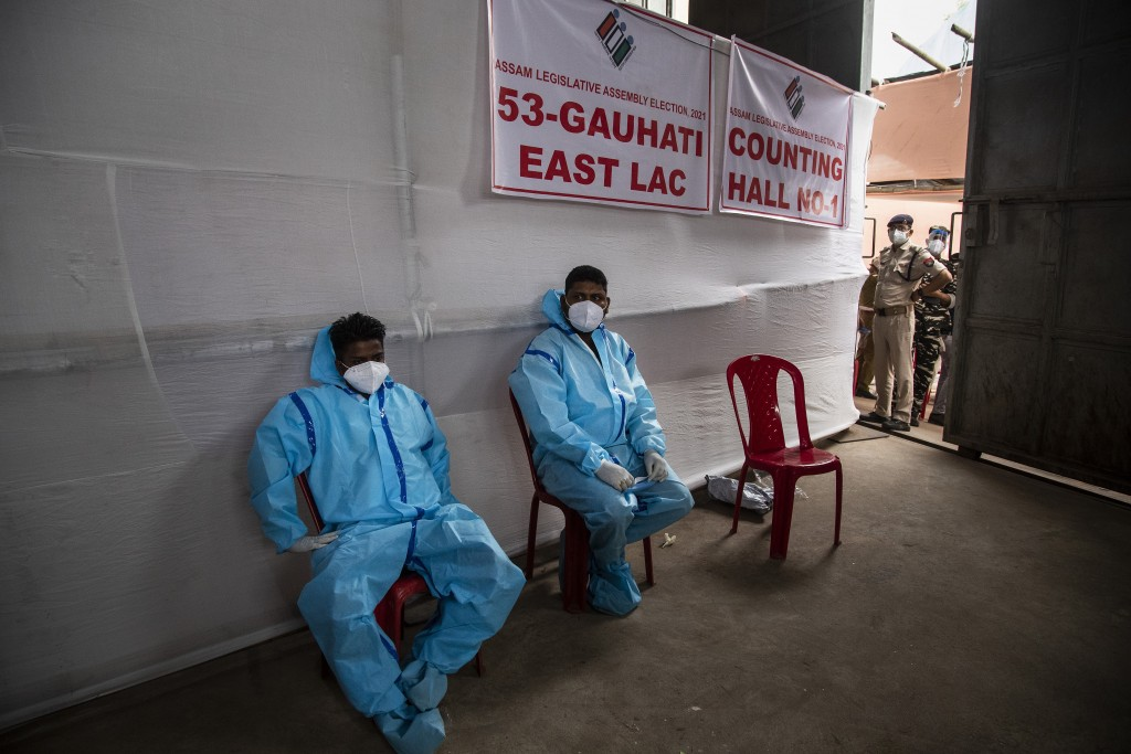 Counting agents in protective suits take rest during the counting of votes of Assam state assembly election in Gauhati, India, Sunday, May 2, 2021. Wi...