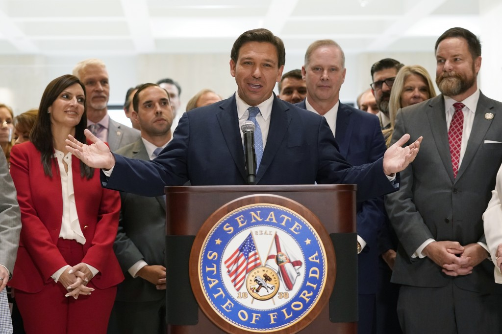 Surrounded by lawmakers, Florida Gov.Ron DeSantis speaks at the end of a legislative session, Friday, April 30, 2021, at the Capitol in Tallahassee, F...