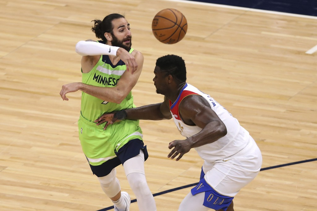 Minnesota Timberwolves' Ricky Rubio (9) passes the ball over New Orleans Pelicans' Zion Williamson during the second half of an NBA basketball game Sa...