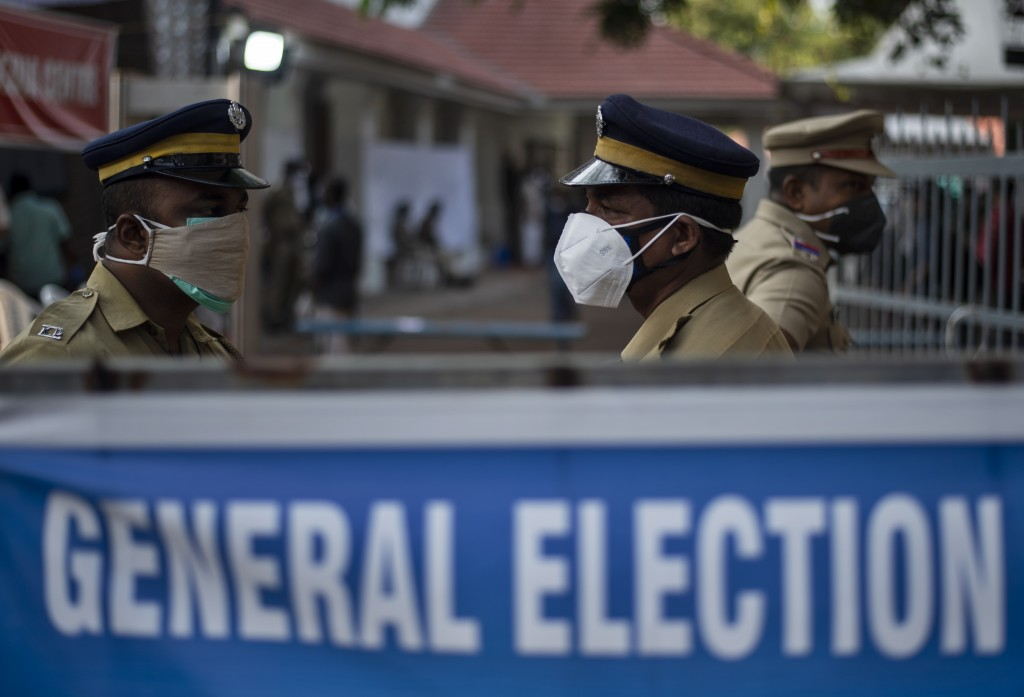 Indian policemen guard at a vote counting center for the state legislature elections amid a weekend lockdown to curb the spread of coronavirus Kochi, ...