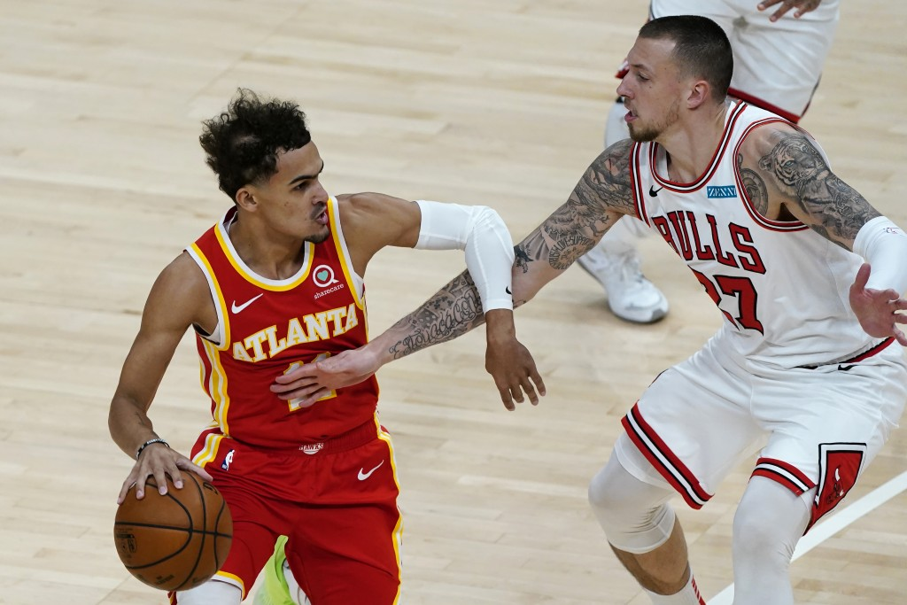 Atlanta Hawks guard Trae Young, left,  tries to get past Chicago Bulls center Daniel Theis, right, in the first half of an NBA basketball game Saturda...