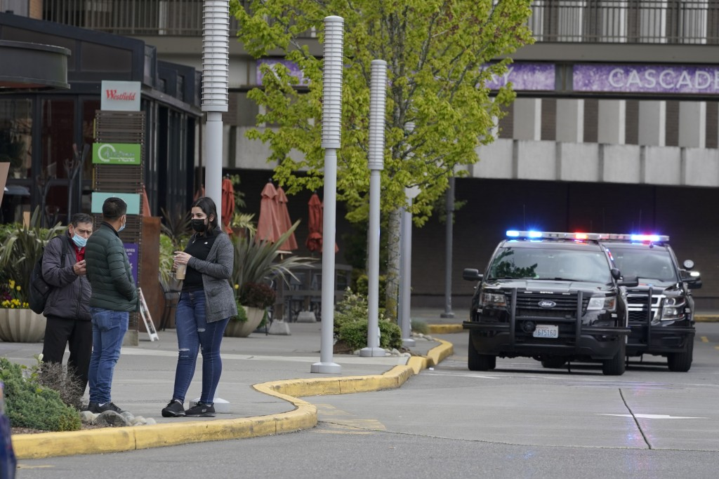 Shoppers evacuated from the Westfield Southcenter Mall stand near a parking lot following a reported shooting, Saturday, May 1, 2021, at the mall in T...