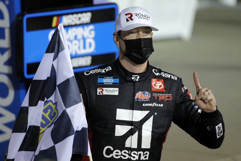 Kyle Busch poses for photos in victory lane after winning a NASCAR Truck Series auto race at Kansas Speedway in Kansas City, Kan., Saturday, May 1, 20...