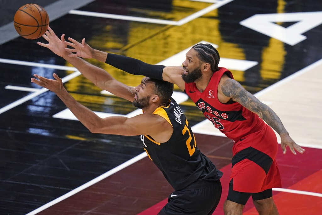Toronto Raptors guard DeAndre' Bembry, right, and Utah Jazz center Rudy Gobert (27) reach for the ball during the second half of an NBA basketball gam...