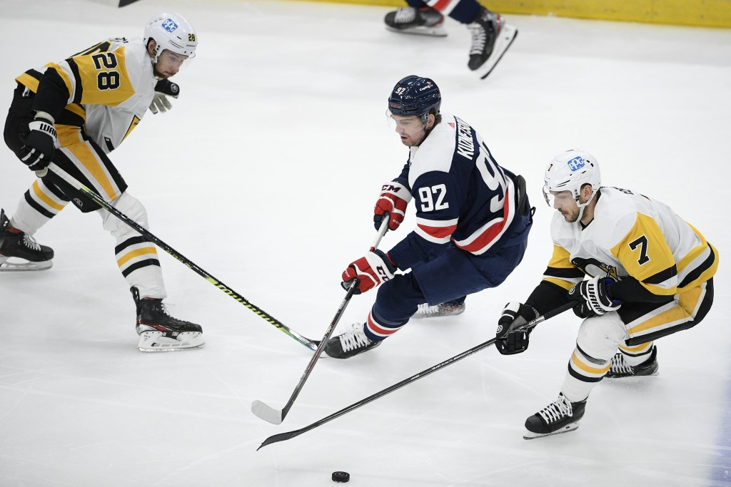 Pittsburgh Penguins defenseman Marcus Pettersson (28) and right wing Colton Sceviour (7) compete for the puck against Washington Capitals center Evgen...
