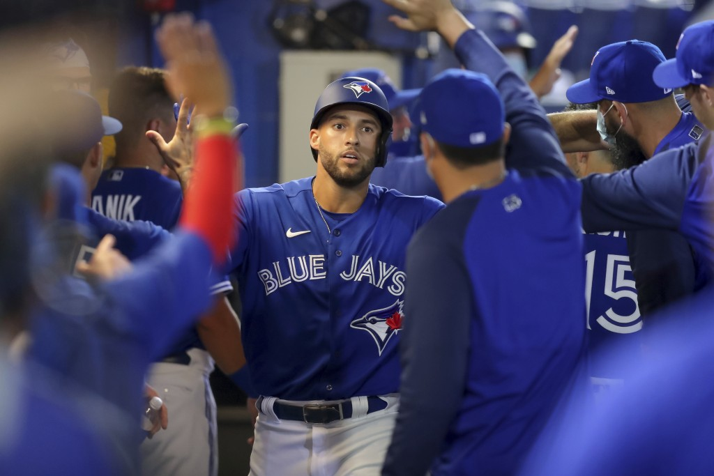 Toronto Blue Jays' George Springer is congratulated after his two-run home run against the Atlanta Braves during the third inning of a baseball game S...