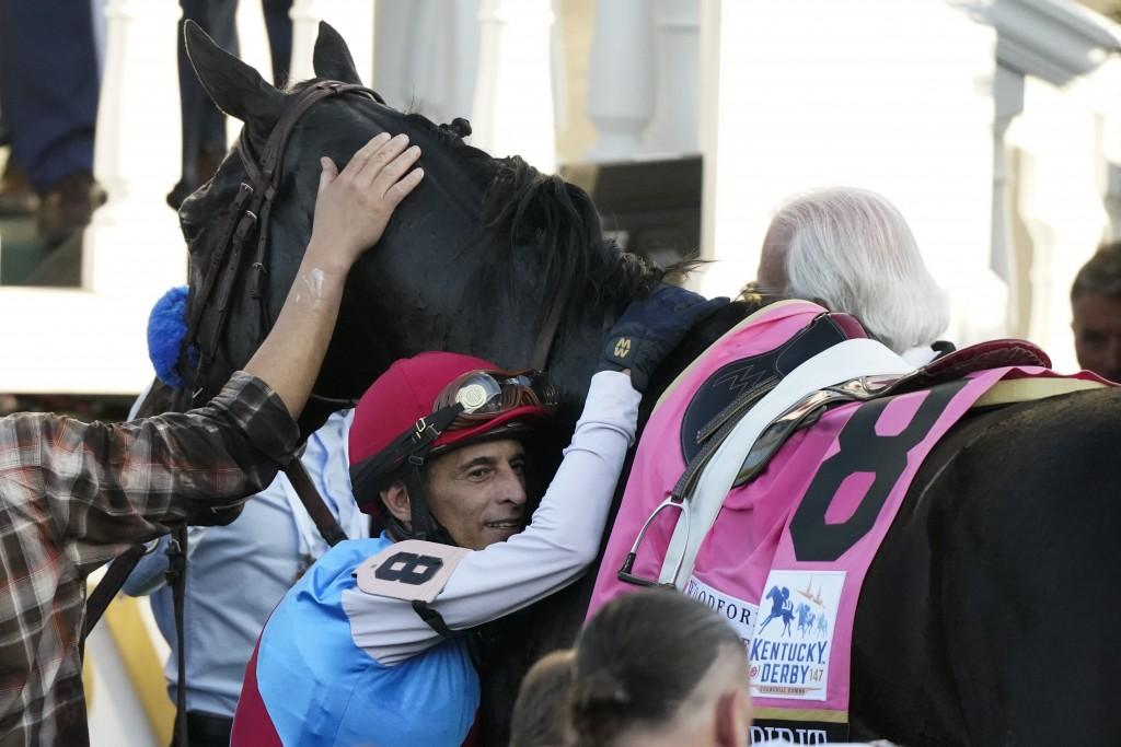 Jockey John Velazquez hugs Medina Spirit in the winner's circle after winning the 147th running of the Kentucky Derby at Churchill Downs, Saturday, Ma...