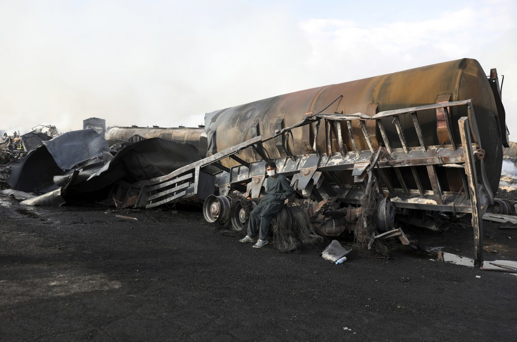 A man sits on his charred fuel tanker in Kabul, Afghanistan, Sunday, May 2, 2021. A fire roared through several fuel tankers on the northern edge of t...