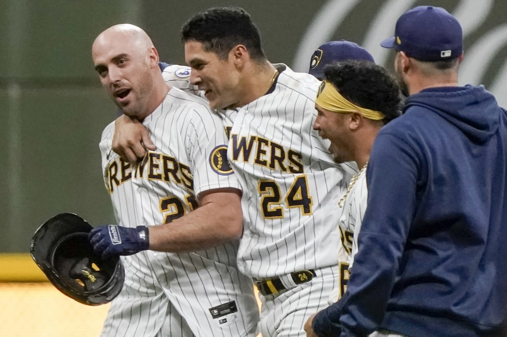 Milwaukee Brewers' Travis Shaw is congratulated after hitting the game-winning RBI single during the 11th inning of a baseball game against the Los An...