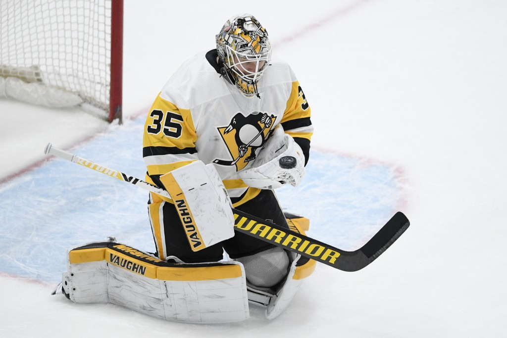 Pittsburgh Penguins goaltender Tristan Jarry stops the puck during the first period of the team's NHL hockey game against the Washington Capitals, Sat...