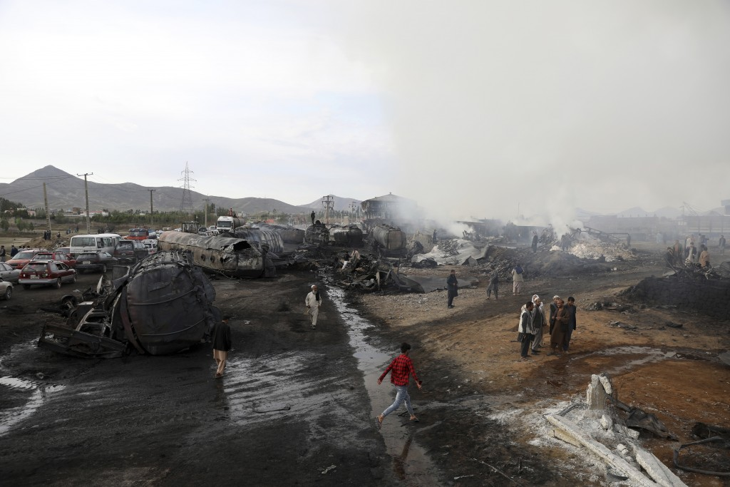 Residents watch burning oil tankers and trucks in Kabul, Afghanistan, Sunday, May 2, 2021. A fire roared through several fuel tankers on the northern ...