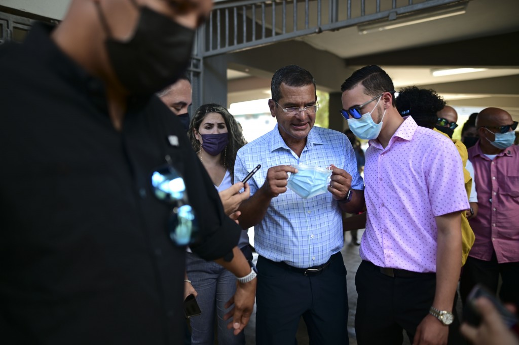 FILE - In this March 10, 2021 file photo, Puerto Rico Gov. Pedro Pierluisi, center, attends a mass vaccination campaign against COVID-19 at the Maria ...