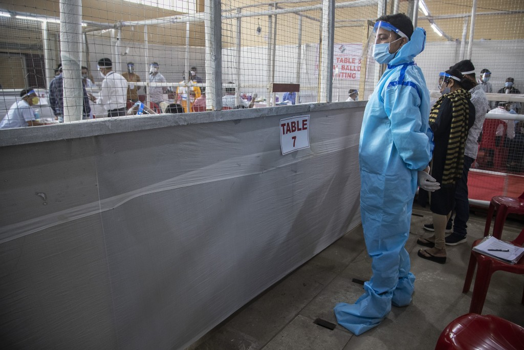A counting agent stands in protective suit during the counting of votes of Assam state assembly election in Gauhati, India, Sunday, May 2, 2021. With ...