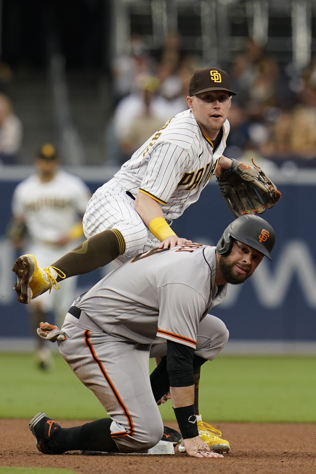 San Diego Padres second baseman Jake Cronenworth, top, watches his throw to first for a double play as San Francisco Giants' Brandon Belt looks on aft...