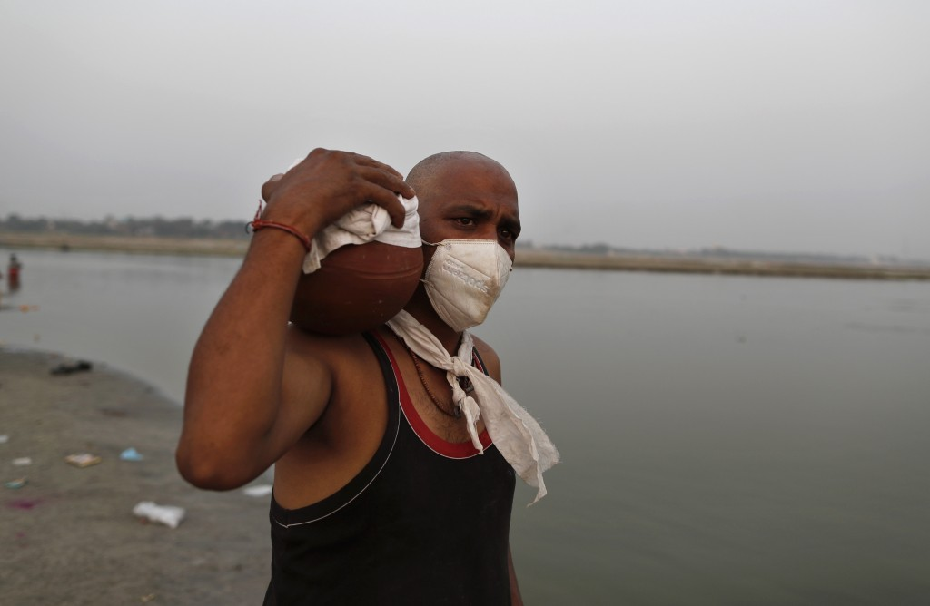 Family member of a COVID-19 victim carries the urn containing the ashes for immersion to perform last rites at Sangam, the confluence of rivers Ganges...