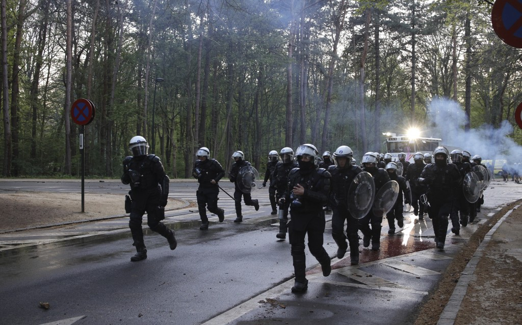 """A group of police run down the street in the Bois de la Cambre park during a party called """"La Boum 2"""" in Brussels, Saturday, May 1, 2021. A few thousa..."""
