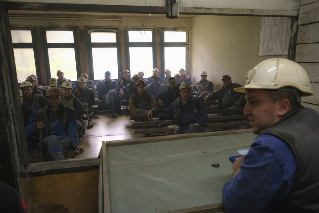 Bosnian coal miners hold a briefing before their shift start at a mine in Zenica, Bosnia, Thursday, April 29, 2021. Arriving for their shift and assem...