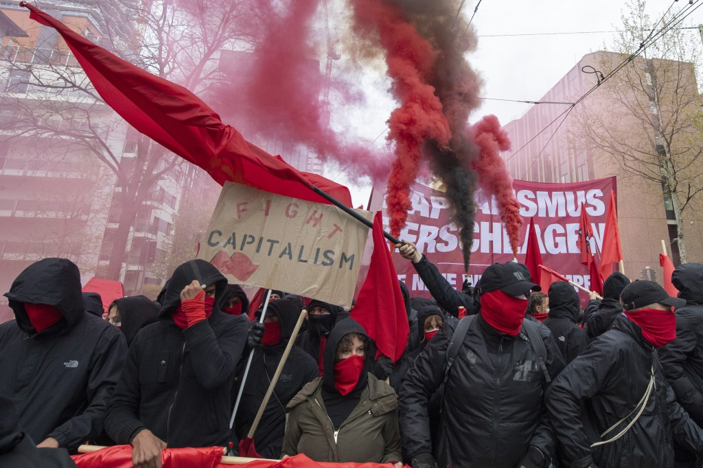 """Hooded participants of the """"Revolutionary May Day Demonstration"""" march in streets in Frankfurt Saturday, May 1, 2021. (Boris Roessler/dpa via AP)"""