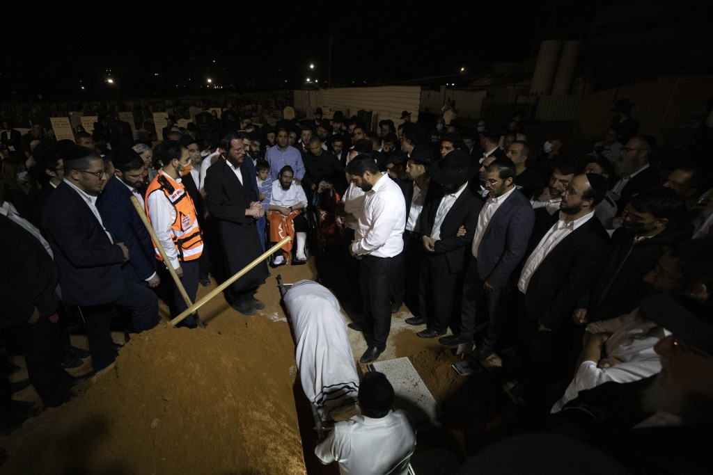 Mourners gather around the grave during the funeral of Yedidyia Chiyuis at a cemetery in Petah Tikva, Sunday, May 2, 2021. A stampede at a religious f...